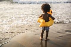 Leuke peuter met eendbuis op het strand Stock Foto's