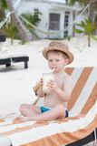 Leuke peuter nippende milkshake op het strand stock fotografie