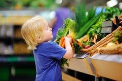 Leuke peuterjongen die in supermarkt verse organische wortelen kiezen Stock Afbeeldingen