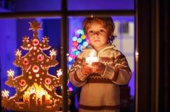 Leuke peuterjongen die zich door venster in Kerstmistijd bevinden en holdin Stock Afbeeldingen