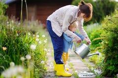 Leuke peuterjongen en zijn jonge moeder het water geven installaties in de tuin Royalty-vrije Stock Afbeelding