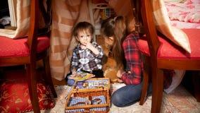 Leuke peuterjongen met oudere zuster in tent bij slaapkamer royalty-vrije stock foto's