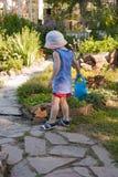 Leuke peuterjongen in strohoed het water geven installaties in de tuin bij de zomer zonnige dag Stock Foto's