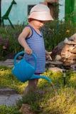 Leuke peuterjongen in strohoed het water geven installaties in de tuin bij de zomer zonnige dag Royalty-vrije Stock Fotografie