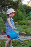 Leuke peuterjongen in strohoed het water geven installaties in de tuin bij de zomer zonnige dag Stock Fotografie