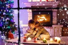 Leuke peuterjongens, het blonde tweelingen spelen samen en lookinig op brand in schoorsteen Familie het vieren Kerstmisvakantie Royalty-vrije Stock Foto's
