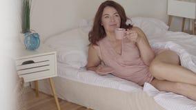Leuke rijpe vrouw het drinken thee of koffie die in bed in de ochtend liggen Glimlachende dame die thuis ontspannen De zon glanst stock video