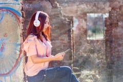 Leuke roodharige tienerdame met digitale tablet het luisteren muziek op hoofdtelefoons en zittingen op de bakstenen van de ruïnes stock foto