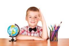 Leuke schooljongen bij zijn bureau, bol en potloden Stock Afbeelding