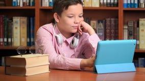 Leuke schooljongen gebruikend computertablet en luisterend aan het lezing stock video