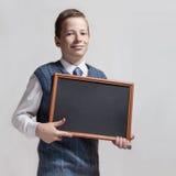 Leuke schooljongen met leeg bord Stock Afbeeldingen