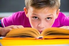 Leuke schooljongenlezing in klaslokaal Stock Foto