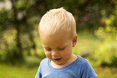 Leuke schuwe peuter tegen aardachtergrond Aanbiddelijke smirkling babyjongen Stock Afbeeldingen