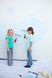 Leuke siblings die een muur schilderen Stock Afbeeldingen
