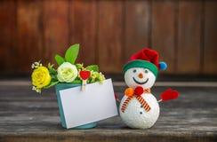 Leuke sneeuwman met lege witte kaart op bloempot over vage houten achtergrond stock fotografie
