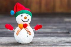 Leuke sneeuwmens over vage houten achtergrond stock afbeelding