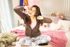 Leuke Spaanse tiener geeuwzitting op bed Stock Afbeelding