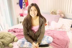 Leuke Spaanse tiener het glimlachen zitting in bed Royalty-vrije Stock Foto