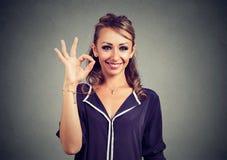 Leuke speelse jonge vrouw die o.k. teken over grijze achtergrond tonen Stock Fotografie
