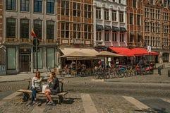 Leuke straat met mensen die op openbare bank in Brussel spreken Stock Afbeelding