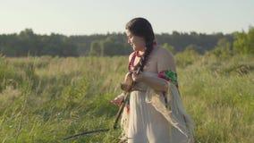 Leuke te zware vrouw die het gras met de zeis op het groene de zomergebied maaien Folklore, tradities Het werk in stock footage