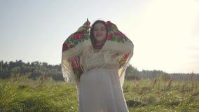 Leuke te zware vrouw die in traditionele sjaal de camera bekijken die zich op de zomergebied bevinden in zonlicht Mooi stock footage