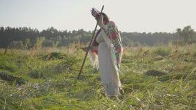 Leuke te zware vrouw met een kroon op haar hoofd die het gras met de zeis op het groene de zomergebied maaien Het werk in stock footage