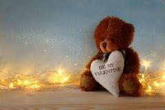 Leuke teddybeerzitting en holding een hart Stock Afbeeldingen