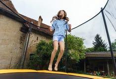 Leuke tiener die op trampoline springen stock foto's