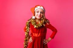 Leuke tiener in Kerstmanhoed en met klatergoud op hals die op rode bedelaars glimlachen royalty-vrije stock fotografie