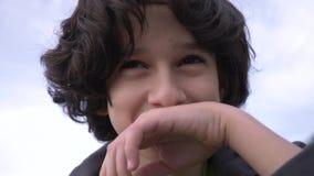Leuke tiener met krullend haar tegen de blauwe hemel 4k, het slow-motion schieten stock footage