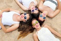 Leuke tienermeisjes die bij hoofden zich samen op zand aansluiten Stock Foto's
