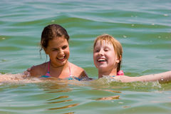 Leuke tienermeisjes die op zee water spelen Stock Afbeeldingen