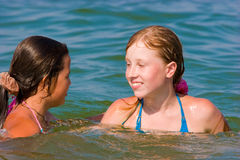 Leuke tienermeisjes die op zee water spelen Royalty-vrije Stock Afbeeldingen