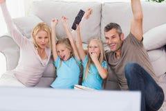 Leuke tweelingen en ouders die wapens opheffen terwijl het letten van op televisie royalty-vrije stock foto's
