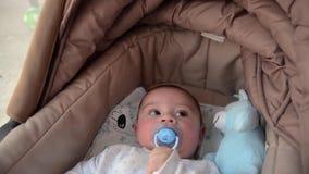 Leuke 3 van de babymaanden oud jongen die grappige gezichten in baby maken wieg dragen stock video