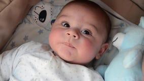 Leuke 3 van de babymaanden oud jongen die grappige gezichten in baby maken wieg dragen stock videobeelden