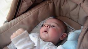 Leuke 3 van de babymaanden oud jongen die grappige gezichten in baby maken wieg dragen stock footage