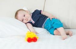 Leuke 10 van de babymaanden oud jongen die op bed liggen en stuk speelgoed auto bekijken Stock Foto's