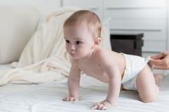 Leuke 9 van de babymaanden oud jongen in luiers die op bed kruipen Stock Afbeeldingen