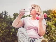 Leuke, volwassen vrouw die oefening in het park op een achtergrond van blauwe hemel en groene bomen op een duidelijke, zonnige da stock foto
