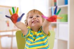 Leuke vrolijke jong geitjejongen die die handen tonen in heldere kleuren worden geschilderd stock afbeelding