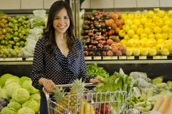 Leuke vrouw bij de kruidenierswinkelopslag Stock Foto