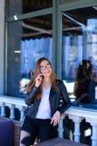 Leuke vrouw die in glazen door smartphone bij straatkoffie spreken Royalty-vrije Stock Foto