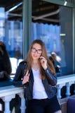 Leuke vrouw die glazen dragen en door smartphone bij straatkoffie spreken Stock Foto