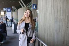 Leuke vrouw die zich dichtbij station in grijze laag bevinden Royalty-vrije Stock Foto's
