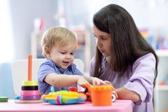 Leuke vrouw met kind het spelen met plastic blokken thuis of kleuterschool stock foto