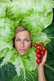 Leuke vrouw met saladebladeren die rond haar hoofdholding worden geschikt sm Stock Foto's