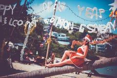 Leuke vrouw in rode kleding, zonnebril en de zitting van de santahoed op palm bij exotisch tropisch strand Vakantieconcept voor N Royalty-vrije Stock Fotografie