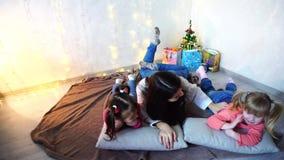 Leuke vrouwelijke en twee voor camera stellen en meisjeskinderen die, die die op kussens, op vloer in ruimte liggen met glimlache stock video